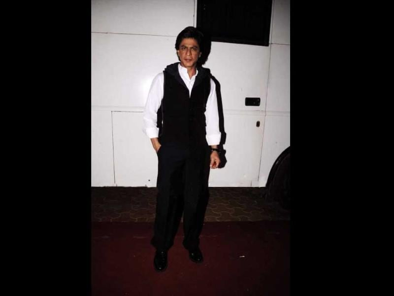 SRK clad in a black waist-coat over white shirt.