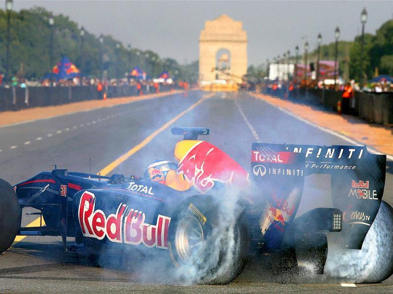 Red Bull Formula One reserve driver Daniel Ricciardo drives near the India Gate during his team's road show in New Delhi.