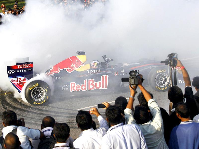 Red Bull Formula One reserve driver Daniel Ricciardo drives near the India Gate during his team's road show in New Delhi. India hosts its maiden Formula One race at the Buddh International Circuit in Noida, on the outskirts of New Delhi, from October 28-30.