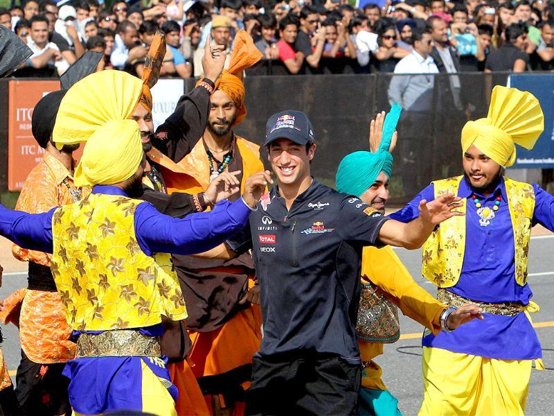 Red Bull racing car of Formula One driver David Ricciardo dances with Folk dancer before the start of a speed event ahead of October 30 Indian Grand Prix, in New Delhi.