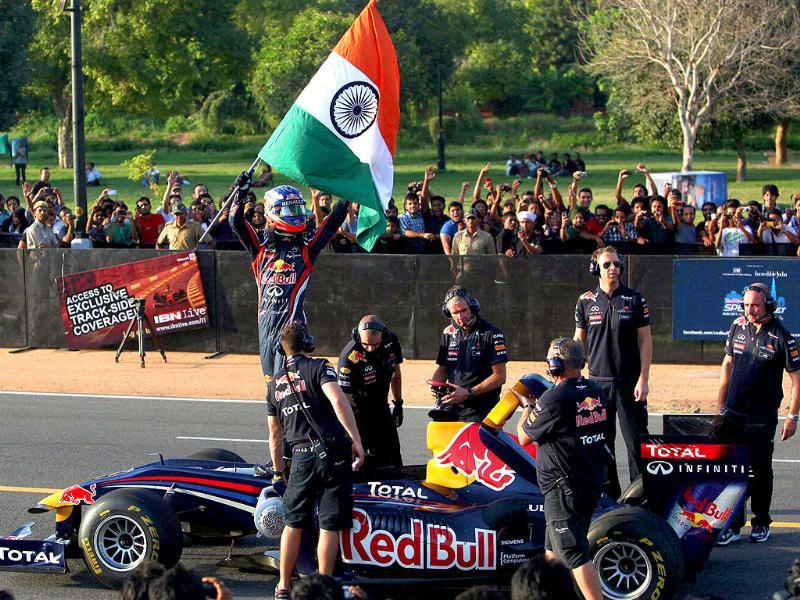 Red Bull supported Formula One racer Daniel Ricciardo holds Indian flag at the end of a speed event ahead of October 30 Indian Grand Prix, in New Delhi.