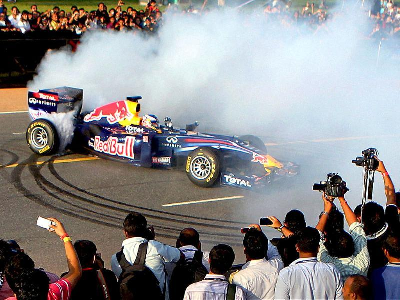 A Red Bull racing car of Formula One burn its tires during a drift at a speed event ahead of October 30 Indian Grand Prix, in New Delhi.