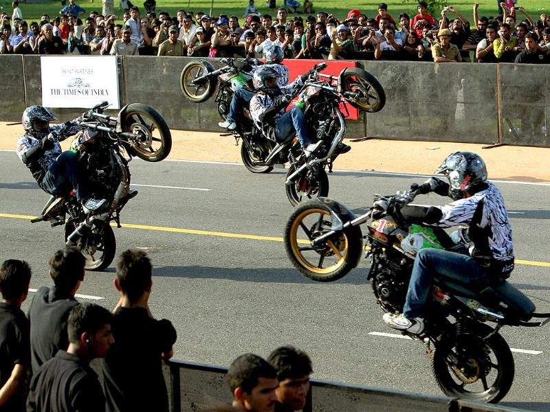 Bikers perform stunts at Rajpath during the Red Bull racing car of Formula One's speed event ahead of October 30 Indian Grand Prix, in New Delhi.