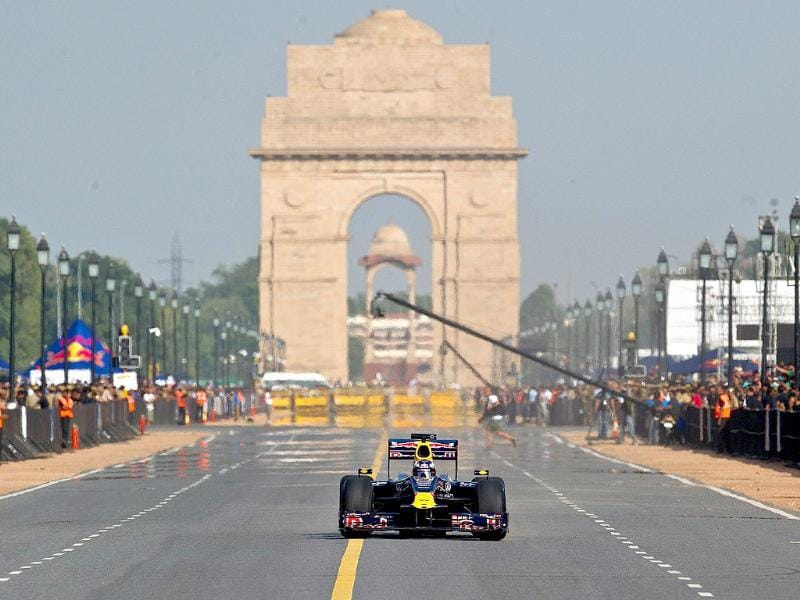 Red Bull Formula One reserve driver Daniel Ricciardo of Australia drives in front of the India Gate during his team's road show in New Delhi.