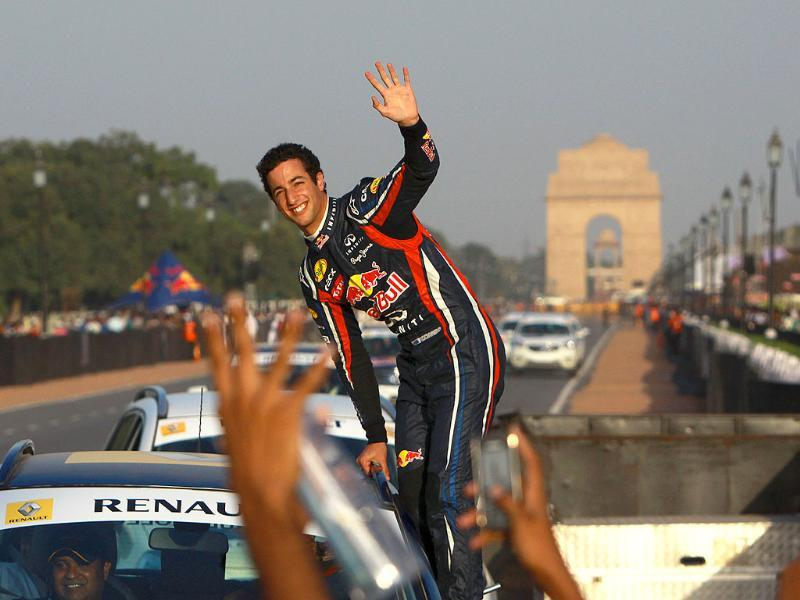 Red Bull racing Formula One driver Daniel Ricciardo waves to the crowd as he powers his Formula One car down a road at India Gate monument at Rajpath in New Delhi.