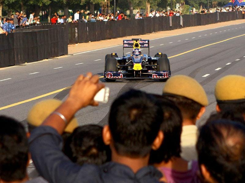 Red Bull Formula One driver Daniel Ricciardo of Australia drives in front of India Gate during his team's road show in New Delhi.
