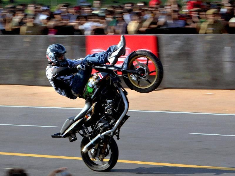 A biker performs stunt at Rajpath during the Red Bull racing car of Formula One at a speed event ahead of October 30 Indian Grand Prix in New Delhi.