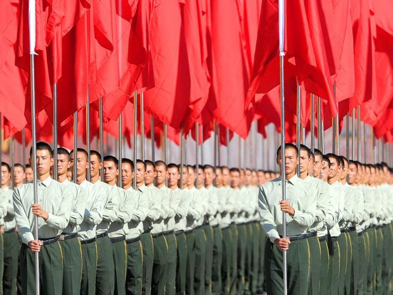 Participants hold red flags during the National Day ceremony at Tiananmen Square in Beijing.
