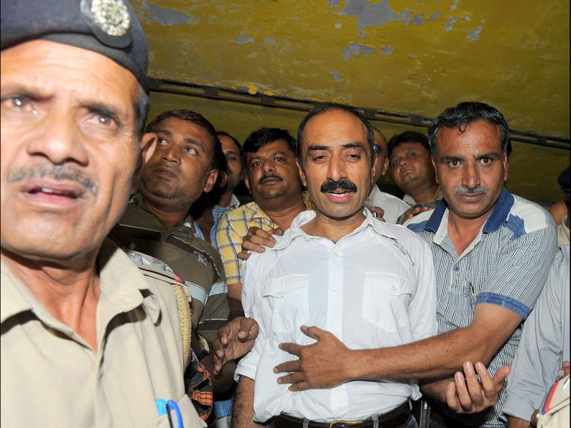 Suspended IPS officer, Sanjeev Bhatt, is escorted by the police as he comes out of additional chief judicial magistrate's court in Ahmedabad.
