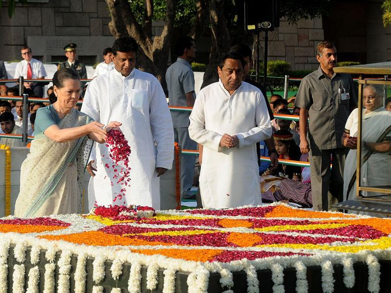 Chairperson of Congress-led UPA government Sonia Gandhi scatters rose petals as she stands alongside minister for transport Kamal Nath while paying her respects at the memorial to the father of the nation Mahatma Gandhi at Rajghat in New Delhi.