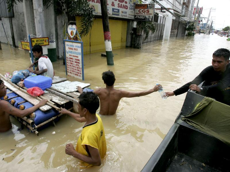 A Philippine Navy rescuer hands his own drinking water to a resident as flooding continues for the fourth day at Calumpit township, Bulacan province north of Manila, Philippines.
