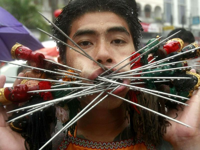 A devotee of the Jui Tui Chinese Shrine has his cheeks pierced with skewers at a procession during the Phuket Vegetarian Festival, southern Thailand.