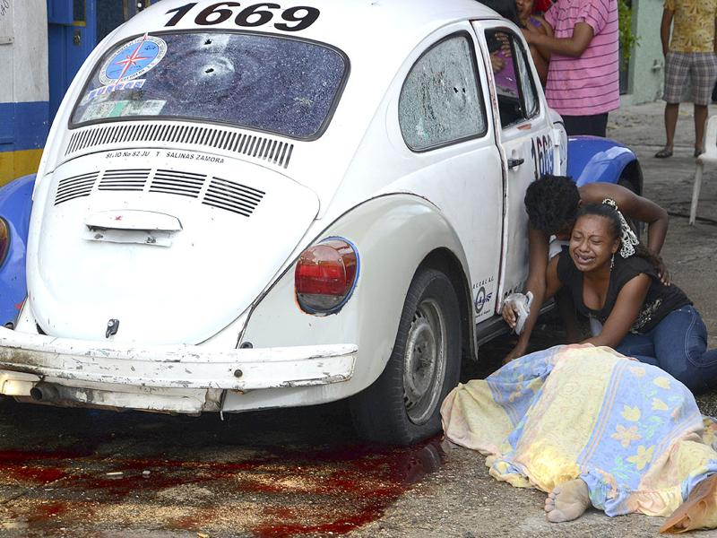 Relatives weep after gunmen opened fire on a taxi killing the driver and the passenger in the Pacific resort city of Acapulco.