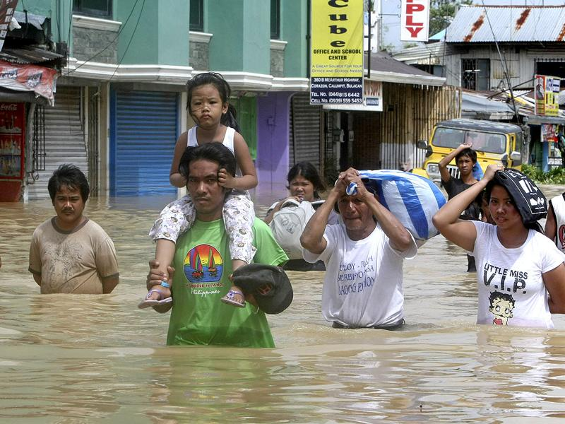 Residents wade through floodwaters with their items as flooding continues for the fourth day at Calumpit township, Bulacan province north of Manila, Philippines.
