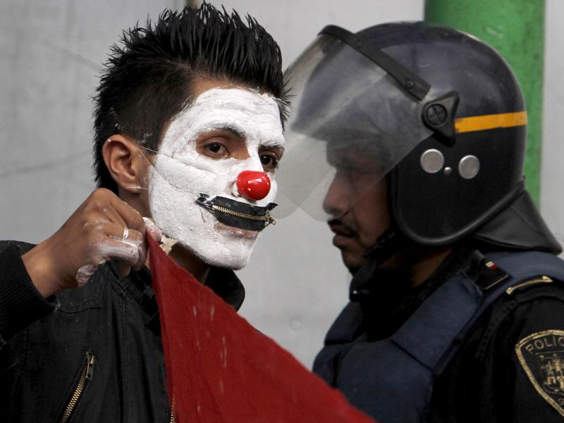 A man with his face painted as clown and wearing a zip on his mouth, demonstrates past a police officer during a march marking the 43th anniversary of the Tlatelolco massacre in Mexico City.