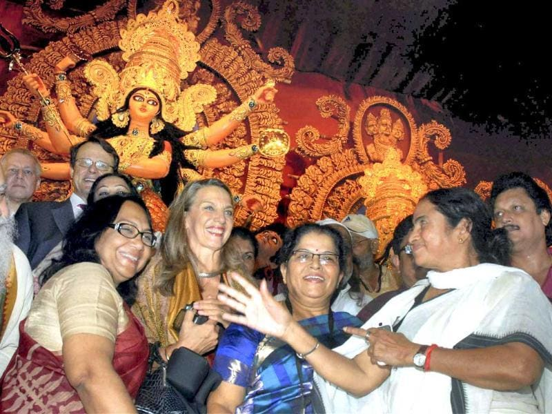 West Bengal chief minister Mamata Banerjee with German tourists celebrates Durga Puja festival in Kolkata.