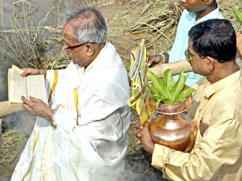 Union finance minister Pranab Mukherjee recites from sacred book Chandi as he performs rituals of Durga puja at his ancestral Mirati village in Birbhum district of West Bengal.