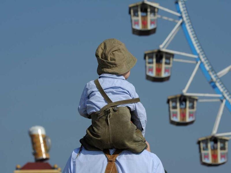A boy wearing traditional Bavarian leather trousers sits on the shoulders of a man as they stand in front of a Ferris wheel at the Theresienwiese fair grounds of the Oktoberfest beer festival in Munich.