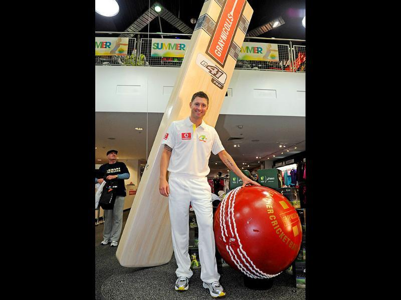 Australian Test cricket captain Michael Clarke models the new Australian Test cricket uniform beside a giant cricket ball and bat in Sydney.