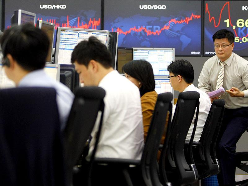Currency traders work at the foreign exchange dealing room of the Korea Exchange Bank headquarters in Seoul, South Korea.