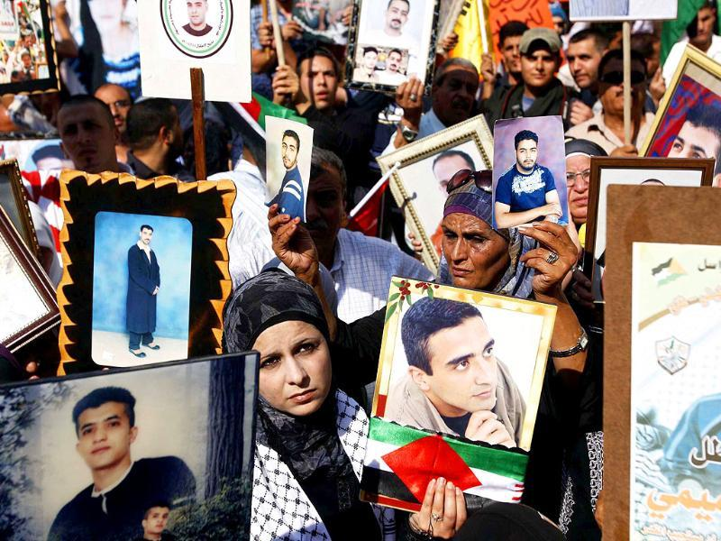 Palestinians hold photographs of their relatives held in Israeli jails during a protest to show solidarity with the prisoners in the West Bank city of Ramallah.