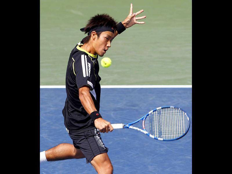 Yuichi Sugita of Japan returns the ball to Milos Raonic of Canada during the Japan Open tennis championships in Tokyo.