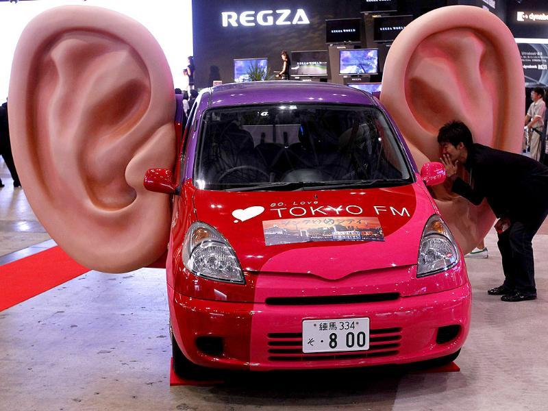 A man talks into a large model of a ear which has recording capabilities on a car at CEATEC JAPAN 2011 electronics show in Chiba, east of Tokyo.