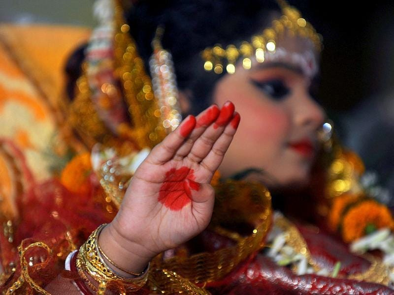 A young girl, known as a 'kumari', is dressed as the Hindu goddess Durga during a ritual for the Durga Puja festival in Siliguri.