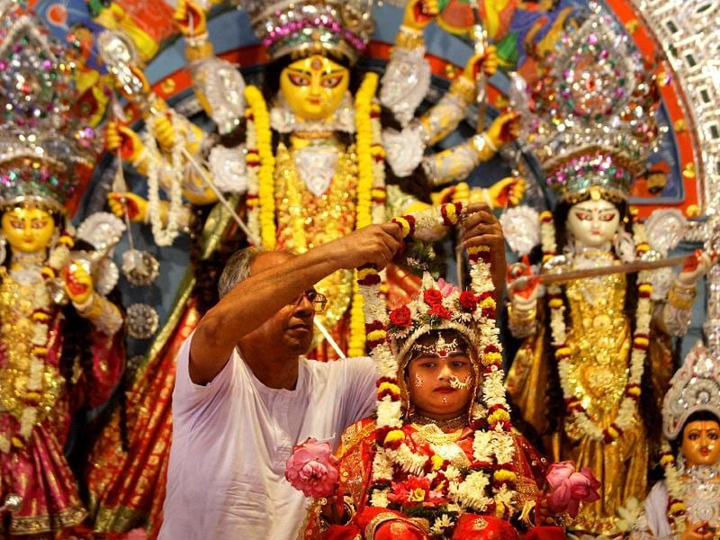 A priest puts a garland on a Kumari, a virgin girl worshipped as an incarnation of Goddess Durga, during Durga Puja festival in Belur.