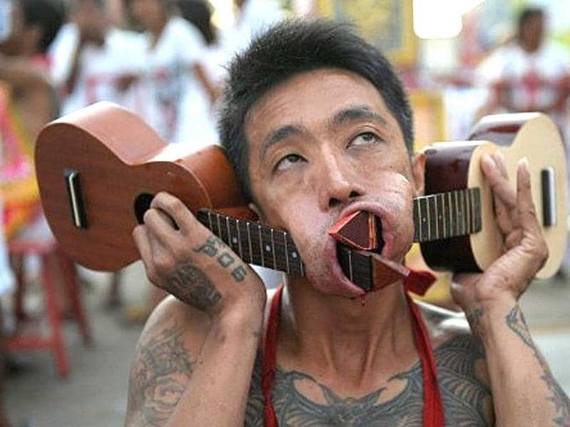 A devotee of the Chinese Bang Neow Shrine parades with two small guitars piercing his cheeks during a street procession to mark the annual Vegetarian Festival in the southern Thai town of Phuket. During the festival, which begins on the first evening of the ninth lunar month and lasts nine days, religious devotees slash themselves with swords, pierce their cheeks with sharp objects and commit other painful acts to purify themselves, taking on the sins of the community.