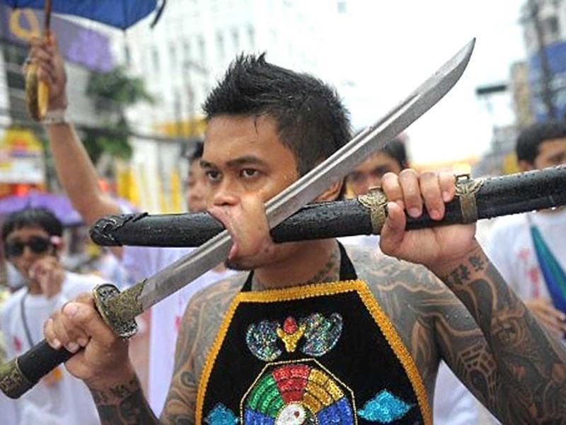 A devotee of the Chinese Jui Tui Shrine parades with a sword piercing his cheek during a street procession marking the annual Vegetarian Festival in the southern Thai town of Phuket. During the festival, which begins on the first evening of the ninth lunar month and lasts nine days, religious devotees slash themselves with swords, pierce their cheeks with sharp objects and commit other painful acts to purify themselves, taking on the sins of the community.