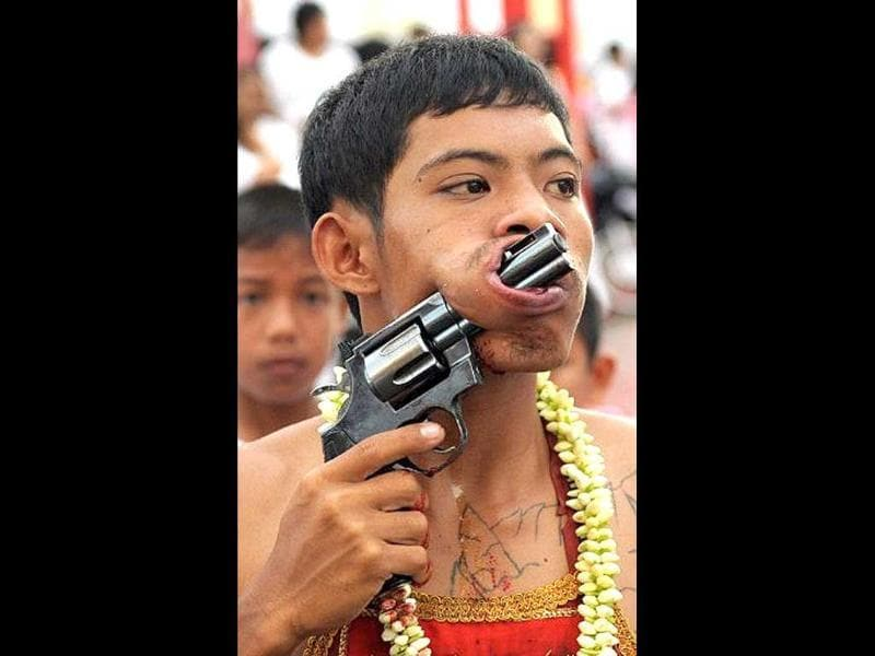A devotee of the Chinese Bang Neow Shrine parades with a gun piercing his cheek during a street procession to mark the annual Vegetarian Festival in the southern Thai town of Phuket.