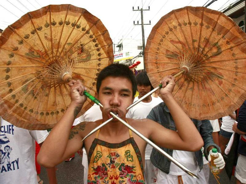 A devotee of the Bang Neow Chinese Shrine has his cheeks pierced with umbrellas during a street procession at the vegetarian festival in Phuket, southern Thailand. The annual nine-day festival, held during the ninth lunar month of the Chinese calendar, celebrates vegetarianism with the belief that the sacred rituals bestow good fortune upon those who religiously observe this rite.