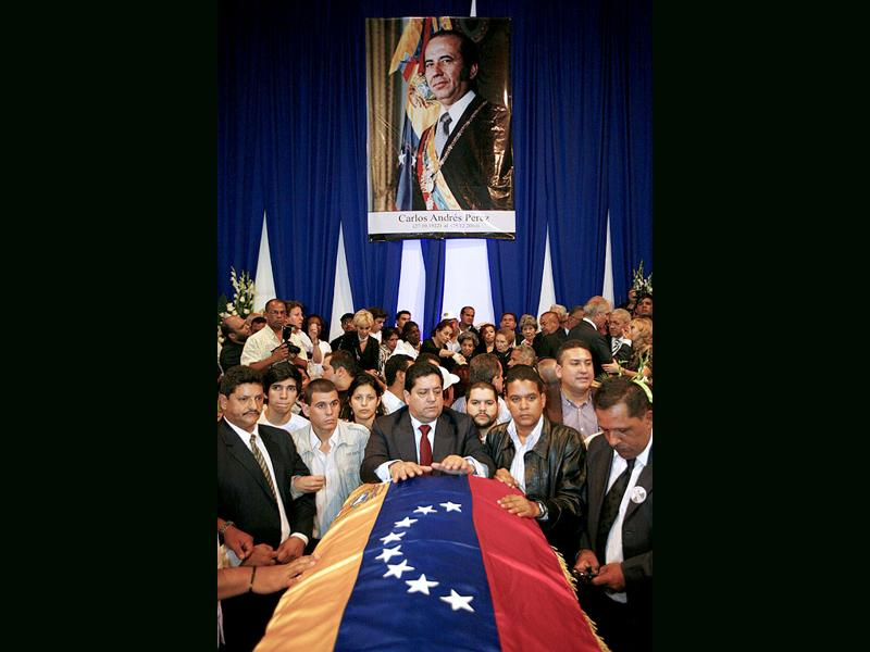 Supporters of former Venezuelan President Carlos Andres Perez rest their hands on his coffin during his funeral in Caracas. Perez was first elected president of Venezuela in 1974 and had a second term beginning in 1989 that was cut short by his impeachment on corruption charges. Perez, 88, died in exile of a heart attack on December 25, 2010.