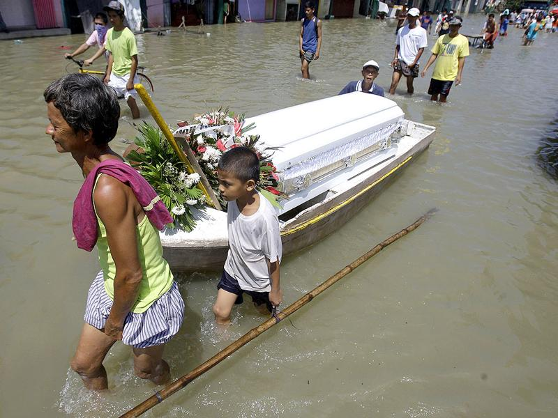 Residents pull a coffin on board a small boat as they wade along the flood-hit area of Calumpit, Bulacan province, north of Manila, on Wednesday. Flooding from back to back typhoons have affected more than half a million people in northern Philippines. The body inside the coffin did not die because of the floods.