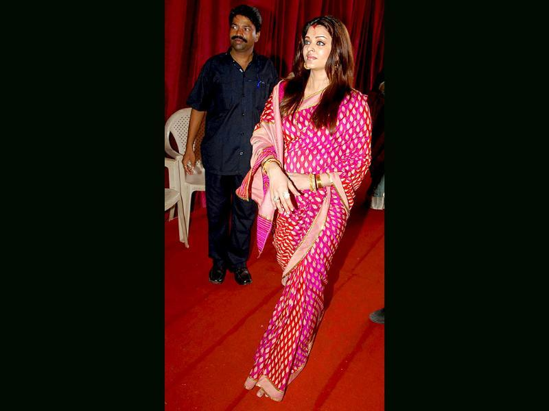 Ash covers up the baby bump as she visits a Durga Puja pandal.