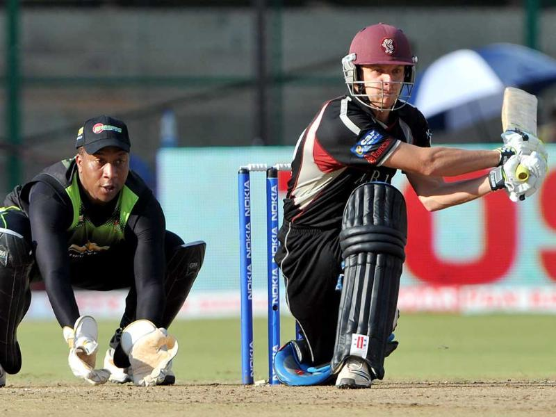 Warriors wicketkeeper Athenkosi Dyili (L) watches as Somerset batsman James Hildreth plays a shot during the Champions League Twenty20 League cricket match between Warriors and Somerset at the M Chinnaswamy Stadium in Bangalore.