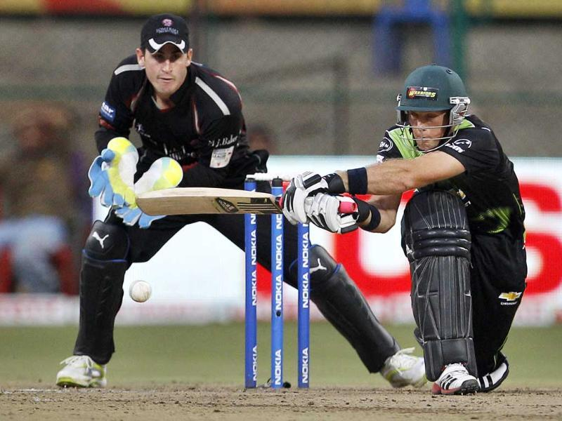 Warriors batsman Colin Ingram (R) plays a shot as Somerset wicketkeeper Craig Kieswetter reacts during their Champions League Twenty20 cricket match in Bangalore.