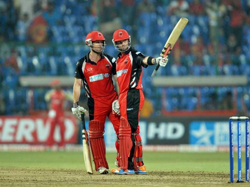 Callum Ferguson of South Australian Redbacks (R) raises his bat after his half century (fifty runs) while teamate Daniel Harris watches during the Champions League Twenty20 League cricket match between Royal Challengers Bangalore (RCB) and South Austrailian Redbacks (SAR) at the M Chinnaswamy Stadium in Bangalore.