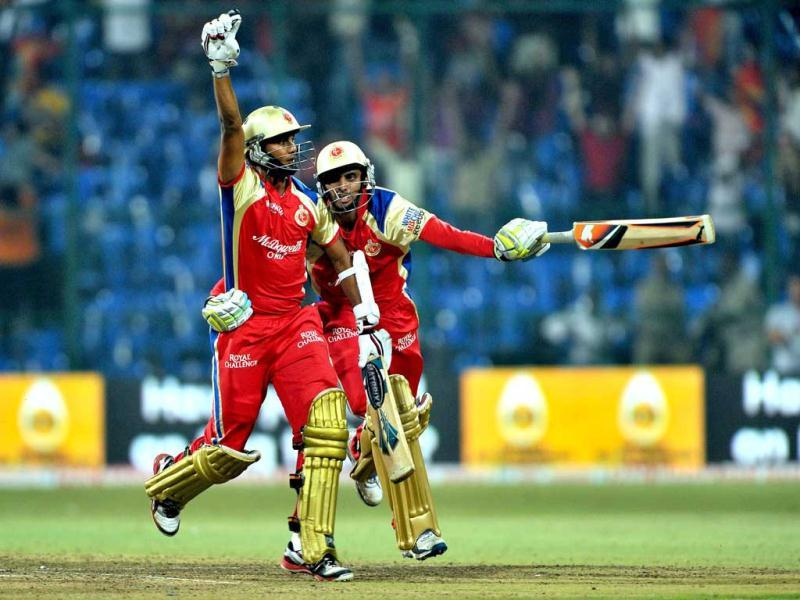 Elated RCB batsmen Arun Karthik (L) and Sreenath Arvind run towards their teammates after their team's victory during the Champions League Twenty20 League match between Royal Challengers Bangalore (RCB) and South Austrailian Redbacks (SAR) at the M Chinnaswamy Stadium in Bangalore.