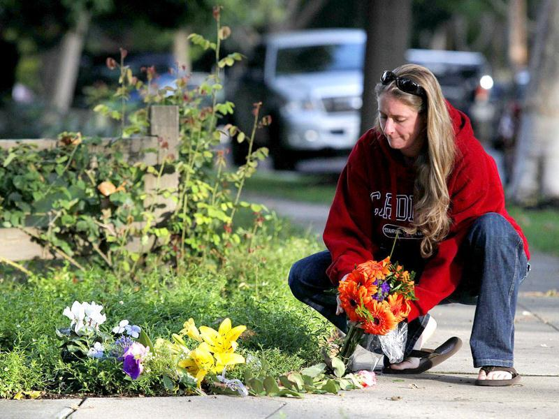 Brandy Faulkner lays flowers outside the the home of Steve Jobs in Palo Alto, California.