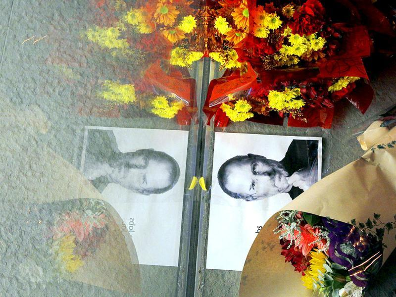 Flowers and a photograph of Steve Jobs are placed against the window outside an Apple store in Boston, Massachusetts.