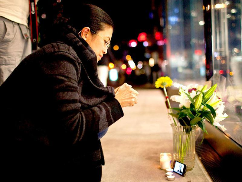 Surina Shukri lights a candle in remembrance of Steve Jobs outside the Apple Store at West 66th Street in New York.