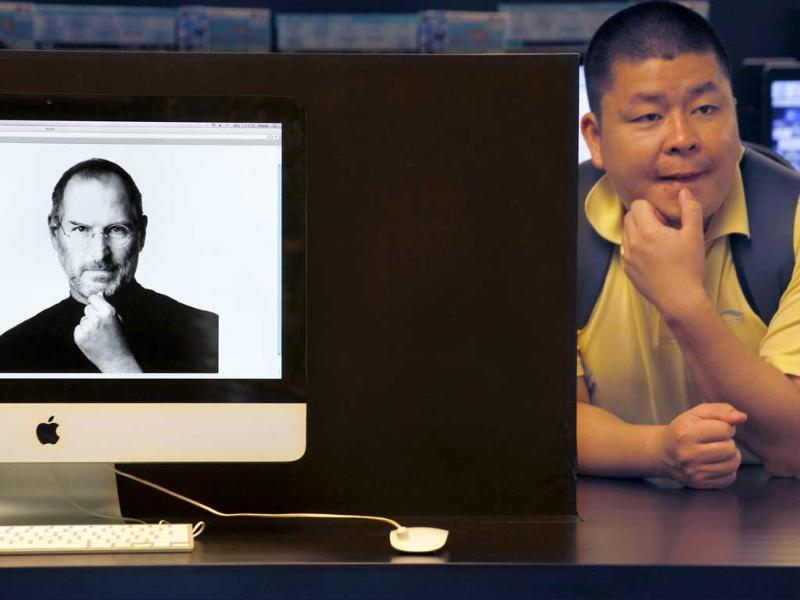 An iMac computer shows the image of Apple co-founder Steve Jobs as a mainland tourist sits near by at an electronic shop in Hong Kong.