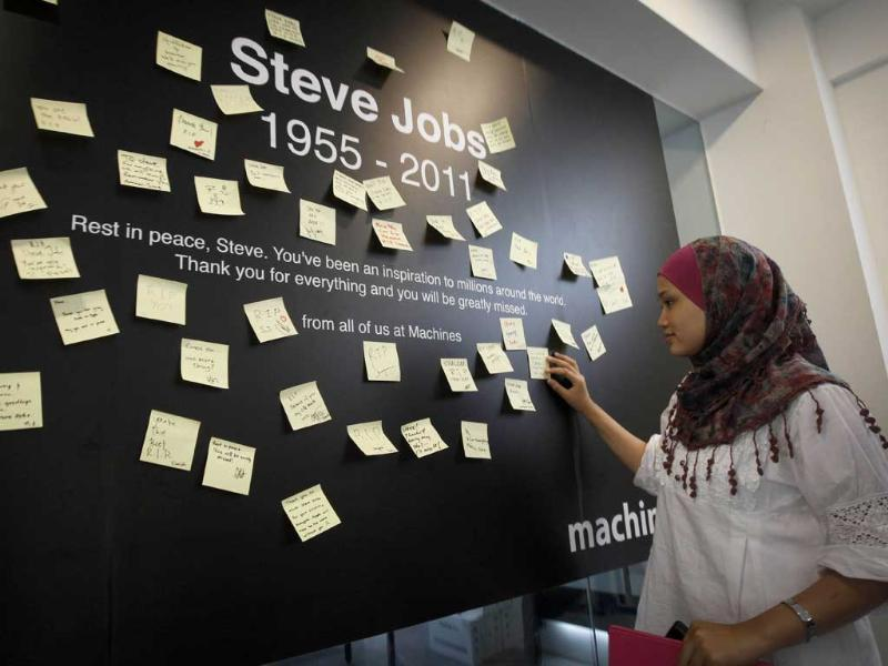 A Malaysian reads condolent notes to pay tribute to Steve Jobs, the Apple founder and former CEO, at an Apple computer outlet in Kuala Lumpur, Malaysia.