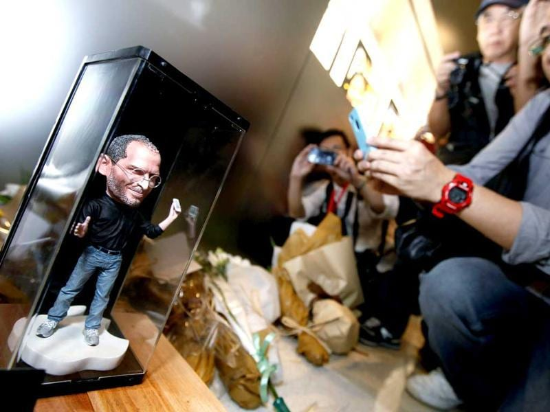 A man takes pictures of a figure of Apple founder and former CEO Steve Jobs near flowers laid in his tribute at an Apple retail store in Hong Kong.