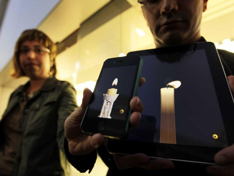 Apple computer fans hold their iPhone and iPad displaying candle graphics during a candle light vigil to pay tribute to Steve Jobs, the Apple founder and former CEO, at an Apple Store in the Ginza shopping district in Tokyo.