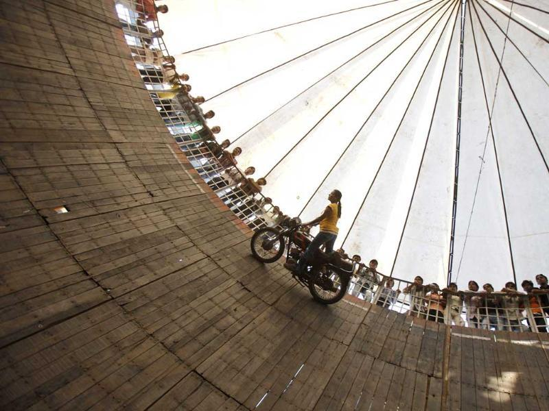 A performer from Maharashtra, performs a stunt as she rides a bike on the walls of the