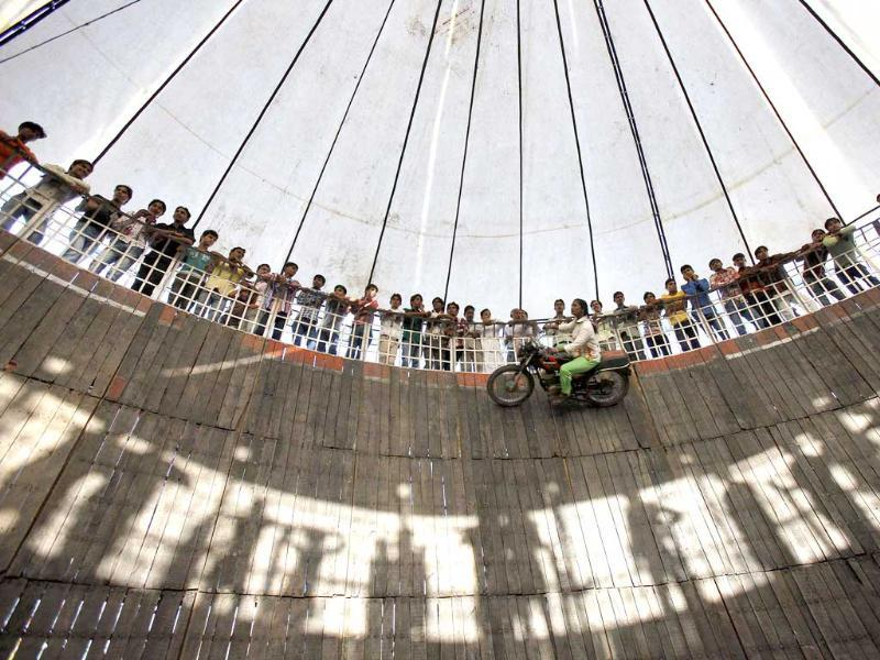 Salma Pathan from Maharashtra, performs a stunt as she rides a bike on the walls of