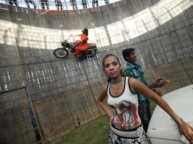 A team member is seen as Salma Pathan, a performer performs a stunt as she rides a bike on the walls of the